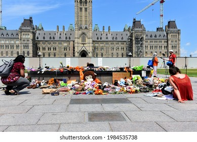 Ottawa, Canada - June 2, 2021: People gather round and leave items near the Centennial Flame on Parliament Hill in memory of the 215 children whose remains were found near former Residential School