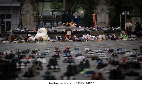 Ottawa, Canada - June 2, 2021: People gather round and leave shoes and toys on Parliament Hill in memory of the 215 children whose remains were found near of former Residential School in Kamloops, B.C