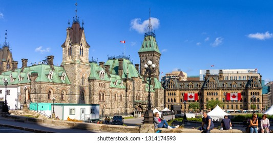 Ottawa, Canada - June 28, 2018: Tourists resting in front of the Parilament of Canada. East Offices and Prime Minister Offices in the background, with the Canada Day festival stage being mounted.