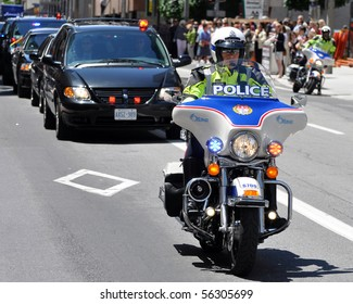 OTTAWA, CANADA - JUNE 30: Policeman on motorcycle leads motorcade transporting Queen Elizabeth II and Prince Philip during their visit to Ottawa.  Ottawa, Ontario, June 30, 2010.