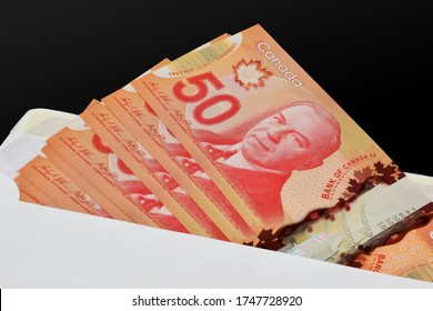 Ottawa, Canada - May 22, 2020: $50 (Fifty) Canadian dollar (CAD) banknotes in an envelope illustrative image concept to symbolize business payment in Canada economy.