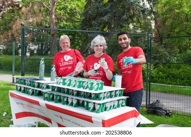 OTTAWA, CANADA  MAY 24, 2014: Unidentified volunteers from the Lung Association, Ontario, offer water at the race finish during the Tamarack Ottawa Marathon Race weekend.
