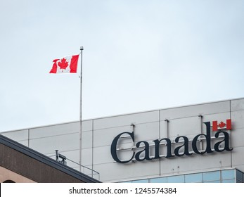 OTTAWA, CANADA - NOVEMBER 10, 2018: Canada Wordmark, the official logo of the Canadian government, on an administrative building next to a Canadian flag waiving