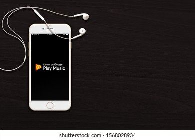 Ottawa, Canada - November 21, 2019: Google Play Music logo displayed on iPhone or smartphone with earphone / headset on wooden background. Illustrative image.