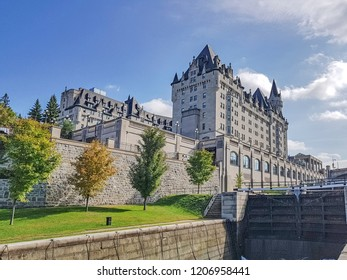 OTTAWA, CANADA - OCTOBER 10, 2018: A view of the Fairmont Chateau Laurier hotel next to the locks of the Rideau Canal in bright  autumnal blue sky
