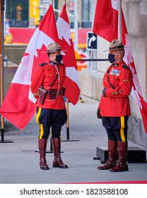 Ottawa, Canada. September 23, 2020.  Two RCMP officers in red uniforms standing in front of Maple leaf flag wearing face masks