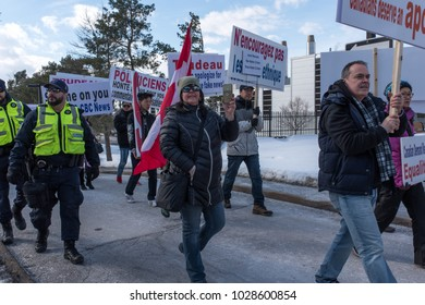 OTTAWA - FEB 18,2018: Canadians demonstrate on Parliament Hill to ask  Prime Minister to stop dividing people and to apologize for taking side with hijab hoaxers. Chinese signs: Asians silent no more!