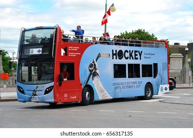 OTTAWA - JUN 3, 2017: Grayline tour bus showing tourists the downtown area is painted with ad for the Hockey exhibit at The Canadian Museum of History. The Canadian capital attracts many tourists.