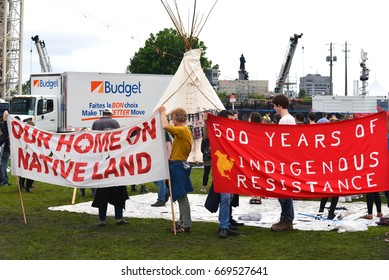 OTTAWA - JUN 30, 2017: Protesters hold signs around the controversial teepee erected as a symbol of rights due to indigenous people that was moved close to the main stage.