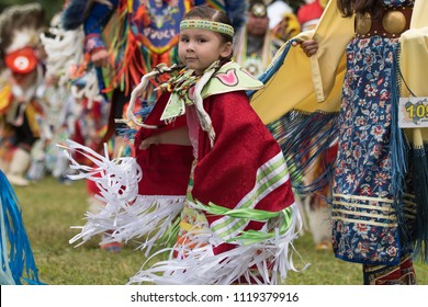OTTAWA - JUNE 23, 2018: Female Pow Wow dancers in colourful outfits at the 2018 Ottawa Summer Solstice Indigenous Festival at Vincent Massey Park with a large group of audience cheering.