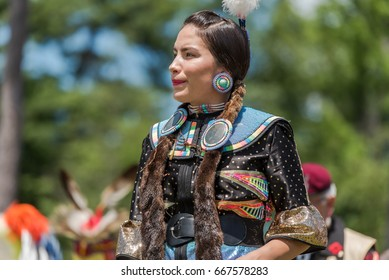 OTTAWA - JUNE 24, 2017: A female Pow Wow dancer at the 2017 Summer Solstice Indigenous Festival at Vincent Massey Park stands still awaiting the drums to start.