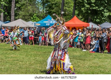 OTTAWA - JUNE 24, 2017: Pow Wow dancers in colourful outfits at the 2017 Ottawa Summer Solstice Indigenous Festival at Vincent Massey Park with a large group of audience taking photos and cheering.