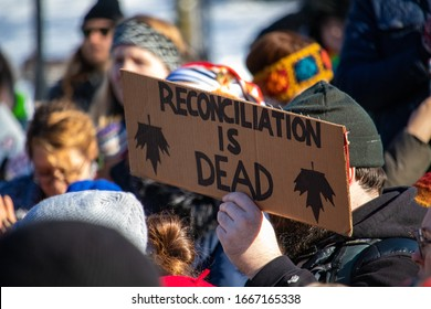 "OTTAWA, ONTARIO, CANADA - FEBRUARY 17, 2019: A sign reads ""Reconciliation is Dead"" and depicts inverted maple leaves at a protest of RCMP intervention in BC's indigenous Wet'suwet'en First Nation."