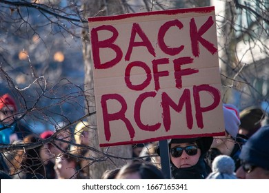 "OTTAWA, ONTARIO, CANADA - FEBRUARY 17, 2019: A sign reads ""Back Off RCMP"" at a protest condemning the actions of Canadian federal police against people of the indigenous Wet'suwet'en First Nation."