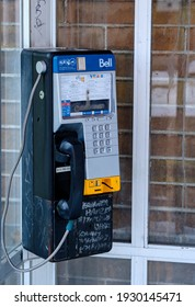 OTTAWA, ONTARIO, CANADA - FEBRUARY 6, 2021: A worn Bell Canada payphone with graffiti in a dirty phone booth on Bank Street in Ottawa.