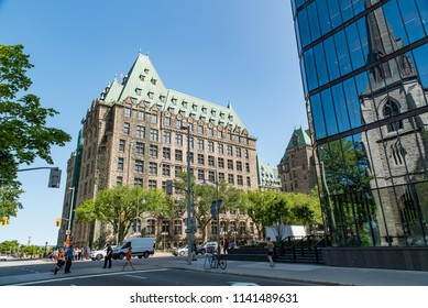 Ottawa, Ontario, Canada - July 12, 2018:  Justice Building as seen from Wellington at Kent Street in summer, reflection of St. Andrew's Presbyterian Church in right building.