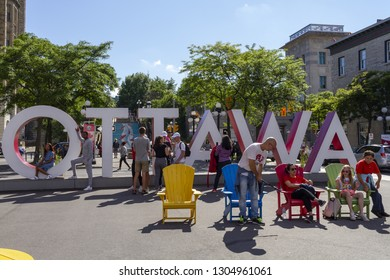 Ottawa, Ontario, Canada - June 28, 2018: Tourists posing at the Ottawa big letters sign on York Street just east of Sussex Drive in Byward Market district.