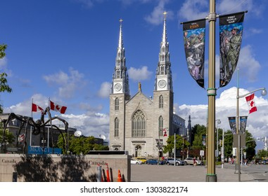 Ottawa, Ontario - June 28, 2018: Notre Dame Cathedral Basilica Otawa and Maman spider scuplture in Ottawa. Banners on poles commemorating the 100th anniversary of the First World War