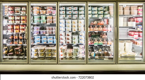 Ottawa, Ontario - September 25, 2017: Different Brands and Flavors of Ice Cream Stacked on Fridge Shelves in a Supermarket. Huge Glass Door Freezer Aisle with Variety Pack of Ice Cream.