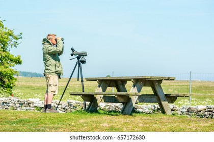 Ottenby, Sweden - May 27, 2017: Environmental documentary. Male birdwatcher looking out over the landscape using binoculars. Spotting scope standing on tripod between him and bench.