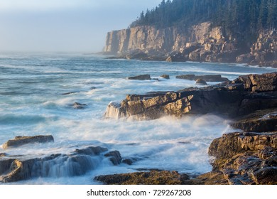 Otter Cliff Acadia National Park Maine at sunrise with fog and rough seas