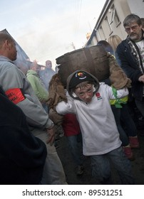 OTTERY ST MARY -  NOVEMBER 5: A young unidentified barrel roller runs through the crowd with a burning barrel at the 2011 Tar Barrels of Ottery Carnival  on  November 5, 2011 in Ottery St Mary