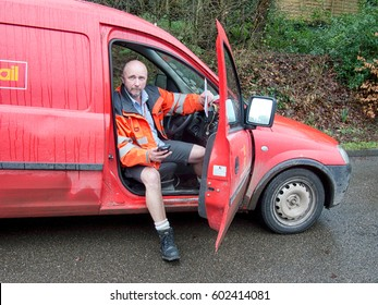 OTTERY ST MARY,  UK – MARCH 8 2017: Rural postal delivery services perform a vital role in small communities throughout the UK, Though costly, many people still welcome a friendly face each morning.