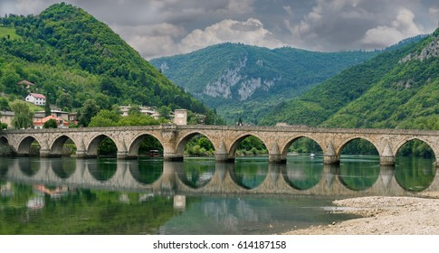 The Ottoman Mehmed Pasa Sokolovic Bridge in Visegrad, Bosnian mountains, with fantastic sky scape and river reflection. Bosnia and Herzegovina.