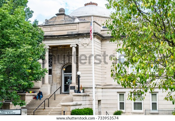 OTTUMWA, IOWA/UNITED STATES - SEPTEMBER 2, 2017: An unidentified man awaits the opening of the Ottumwa Public Library.  The domed stone building is a landmark in Ottumwa, Iowa.