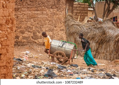 OUAGDOUGOU, BURKINA FASO - JULY 26, 2010: Two young boys towing a can of water in the slums of Ouagadougou in order to distribute water to the inhabitants, Burkina Faso.