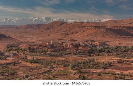 Ouarzazate, Morocco, Africa - January 15, 2014: Panoramic view of a small village surrounded by crops and the mountain range of snowy mountains Atlas in the background, Sahara, Morocco