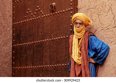 Ouarzazate, Morocco - July 27,2015 :Unidentified Berber dressed his traditional clothes and turban and stands in front of the entrance of an ancient city called Ait Benhaddou kaspar