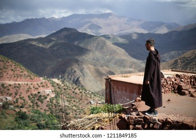 Ouarzazate, Morocco - October 5, 2018: Tourist with traditional moroccan jilbab standing in front of a Green olive trees and valley with old Berber villages in Atlas Mountains near Ouarzazate