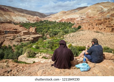 Ouarzazate, Morocco - October 5, 2018: Tourist is sitting with local moroccan man in traditional jilbab in front of a Green oasis valley with old Berber villages in Atlas Mountains near Ouarzazate