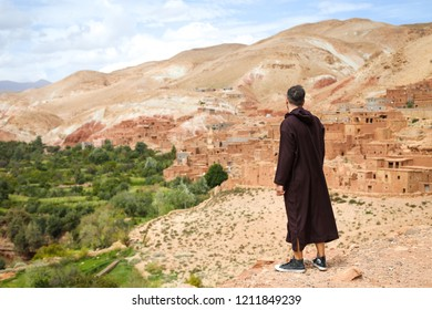 Ouarzazate, Morocco - October 5, 2018: Tourist with traditional moroccan jilbab standing in front of a Green oasis valley with old Berber villages in Atlas Mountains near Ouarzazate