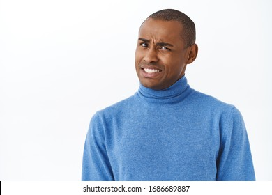 Ouch that hurts. Portrait of embarrassed and awkward young man cringe, grimacing and looking pity camera, feel discomfort trying to say something with caution, white background