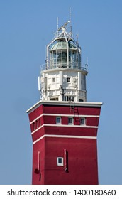 Ouddorp, The Netherlands, April 19, 2019: close-up of the upper section of the red and white lighthouse on the western tip of the island of goeree against a blue sky on a sunny day