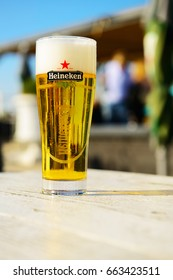 Ouddorp, Netherlands - June 10, 2017: A glass of cold Heineken beer standing on a table in a beach club.