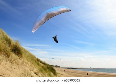 Ouddorp, Netherlands- June 4, 2017: Para gliders flying above de dunes and coast having a great time.