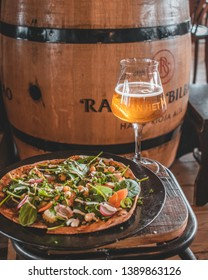 Ouddorp / The Netherlands - March 11 2019: Italian vegetarian pizza with green leaves, spinach, carrots and radishes enjoyed with a beer rustic interior