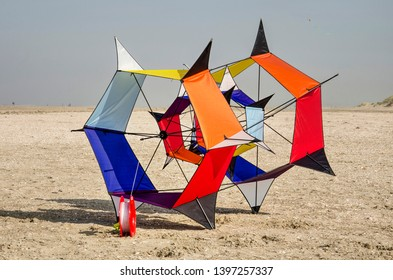 Ouddorp, The Netherlands, October 6, 2018: hexagonally shaped kite with various vibrant colors on the beach with sea and dunes in the background