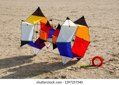 Ouddorp, The Netherlands, October 6, 2018: Multi-colored kite with a complex frame based on hexagons on a sandy surface