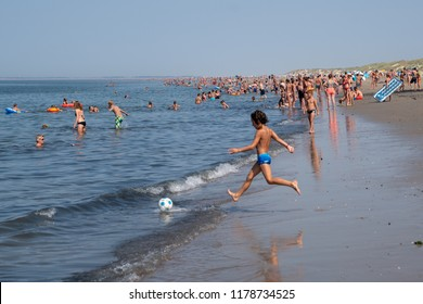 Ouddorp /The Netherlands - Aug. 7, 2018: Summer scene with people swimming, walking and playing at the normally very quiet beach of Ouddorp on Goeree-Overflakkee, The Netherlands.