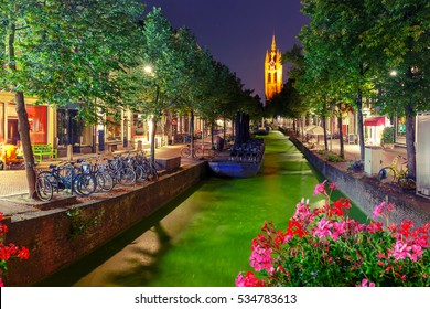 Oude Delft canal and leaning tower of Gothic Protestant Oude Kerk church at night, Delft, Holland, Netherlands. Used toning