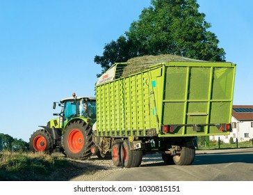 Ouhans, France - August, 25, 2016: Tractor with trailer full of hay on the road in Bourgogne-Franche-Comte region, France.