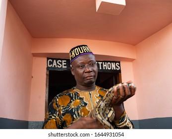 Ouidah, Benin - 30/12/2019.  Vodun priest showing a Python Regius snake at the Temple Of Pythons