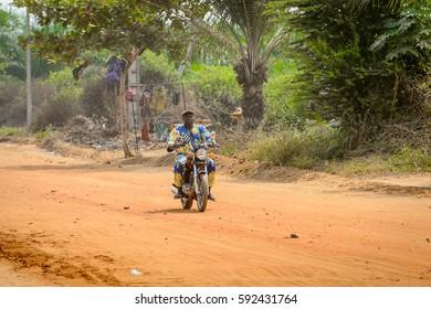 OUIDAH, BENIN - Jan 10, 2017: Unidentified Beninese man rides a motorbike on the street in rush hour. It's a popular way of transportation