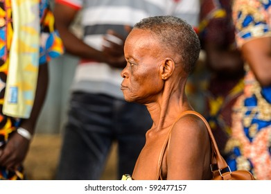 OUIDAH, BENIN - Jan 10, 2017: Unidentified Beninese old woman carries a bag on her shoulder at the voodoo festival, which is anually celebrated on January, 10th.