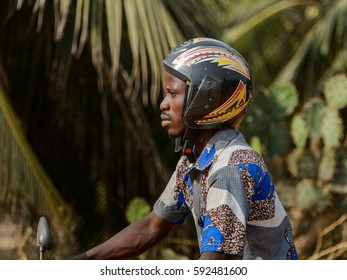 OUIDAH, BENIN - Jan 10, 2017: Unidentified Beninese man in helmet rides a motocycle in colored shirt. Benin people suffer of poverty due to the bad economy