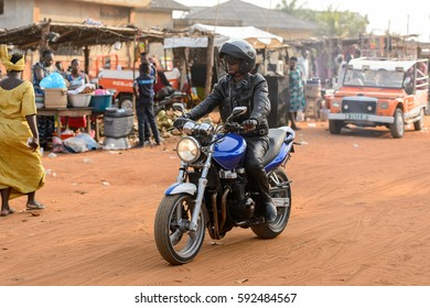 OUIDAH, BENIN - Jan 10, 2017: Unidentified Beninese man rides a motorcycle at the local market. Benin people suffer of poverty due to the bad economy